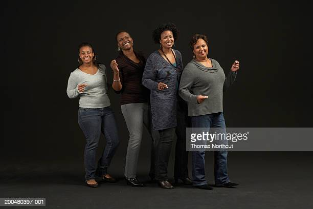 Four women standing side by side, dancing and snapping fingers