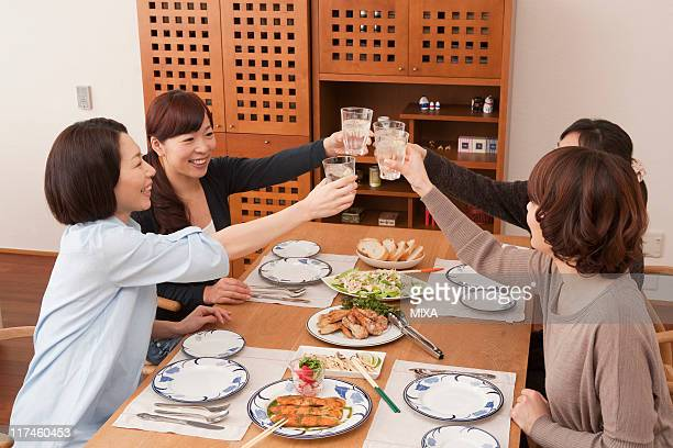 Four women toasting at table