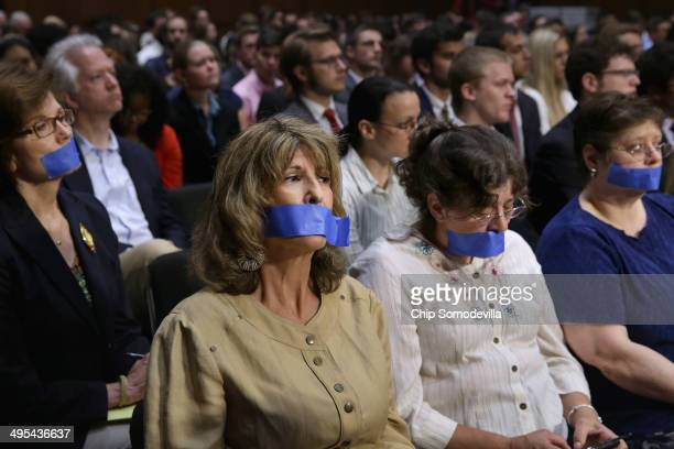 Four women wear blue tape over their mouths as a silent protest during a hearing of the Senate Judiciary Committee about political donations and...