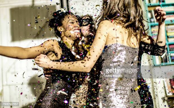 Four women wearing cocktail dresses dancing in a shower of confetti.