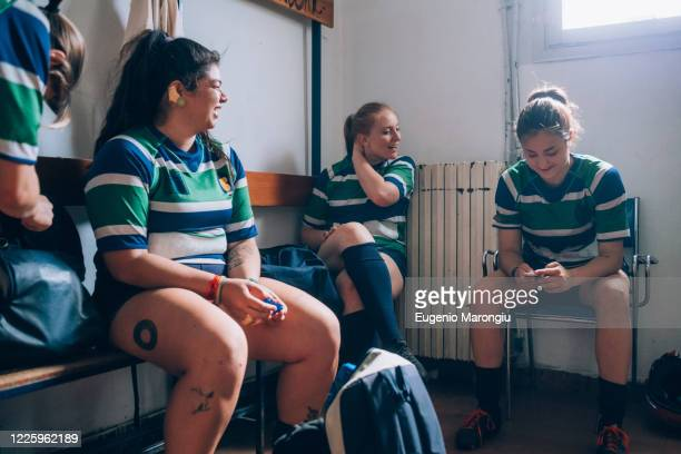 four women wearing green, blue and white rugby shirts sitting in a changing room. - rugby stock pictures, royalty-free photos & images