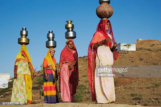 Four women wearing sari carrying water from well