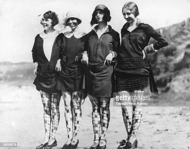 Four women wearing their own design of stockings which are actually drawn on their legs with charcoal