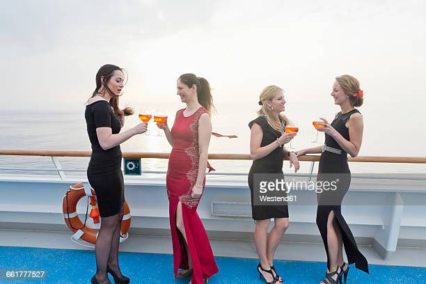 Four women with aperitives standing on deck of a cruise liner