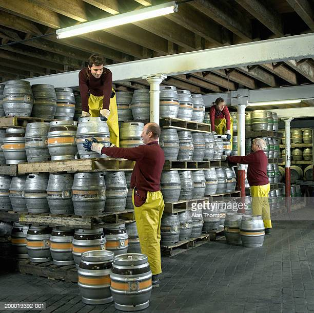 Four workers moving barrels in cellar