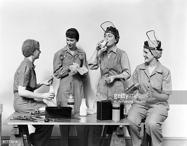 four world war 2 women taking a lunch break all wearing coveralls & 2 wearing raised face masks one is drinking from a pint bottle of milk thermos sandwich. - world war ii stock pictures, royalty-free photos & images