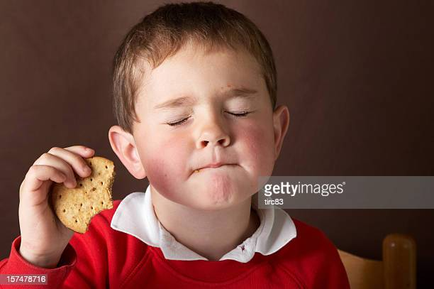 Four year old boy eating chocolate biscuit