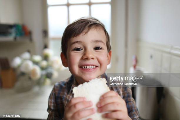 a four year old boy eating sliced bread in the kitchen - espressione del viso foto e immagini stock
