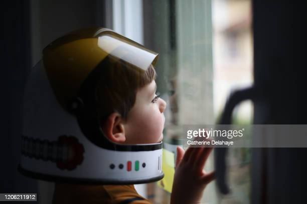 a four year old boy wearing a cosmonaut helmet, looking out the window - futuristisch stockfoto's en -beelden