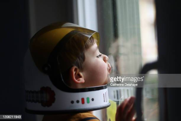 a four year old boy wearing a cosmonaut helmet, looking out the window - space helmet stock pictures, royalty-free photos & images