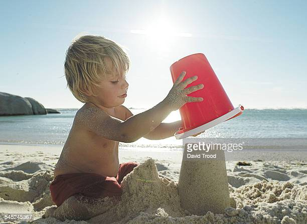 Four year old boy with red bucket in the sand.