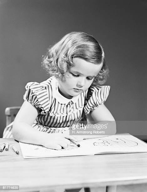 Four year old girl at desk in school classroom, coloring crayon in book.