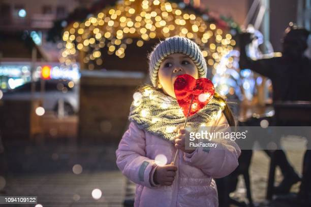 four year old girl enjoying christmas candy - christmas market stock pictures, royalty-free photos & images