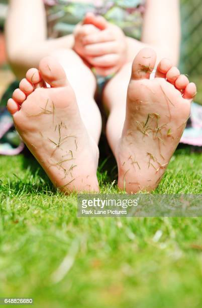 Four year old girl in a garden with grass cuttings on the soles of her feet.