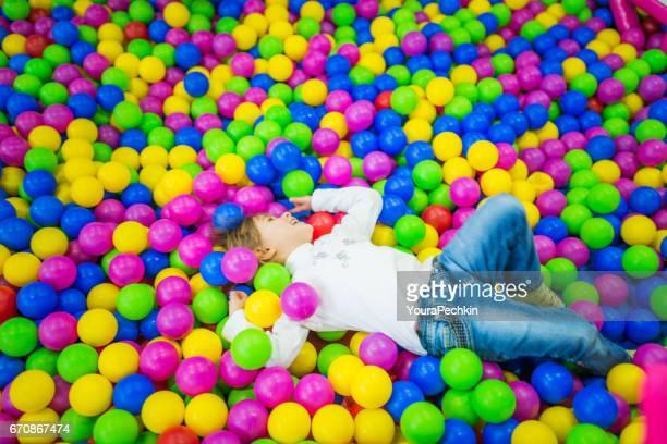 Niña de cuatro años en una piscina de bolas de colores