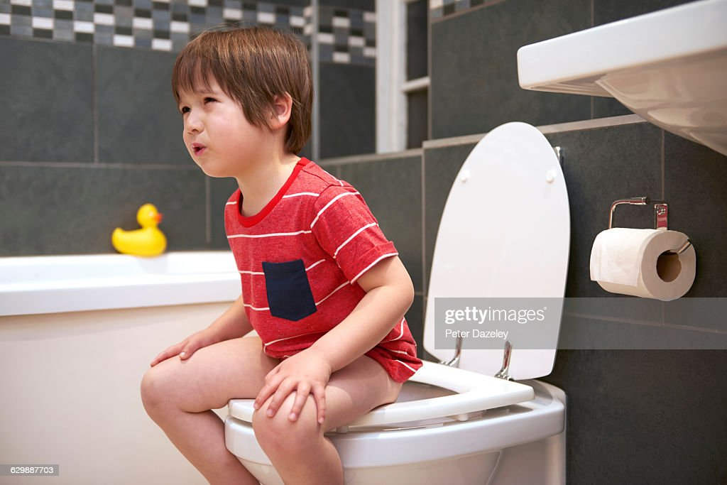 Four year old in pain on the toilet : Stock Photo