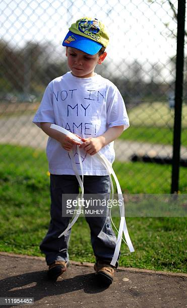 Four year old James McCullough of Omagh hands out white ribbons and wears a tshirt with the words 'Not in my name' is support of murdered Police...