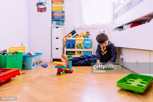 Four years old boy playing in his bedroom with a lot of toys