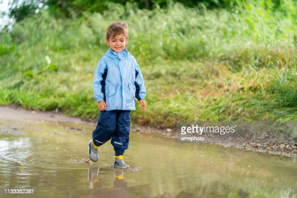 four years old cute boy walking through rain puddle - 4 5 years stock pictures, royalty-free photos & images