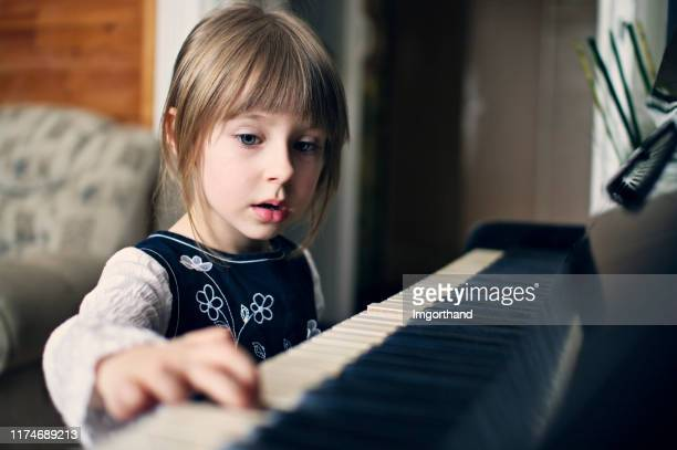 four years old girl playing piano and singing - 4 5 years stock pictures, royalty-free photos & images