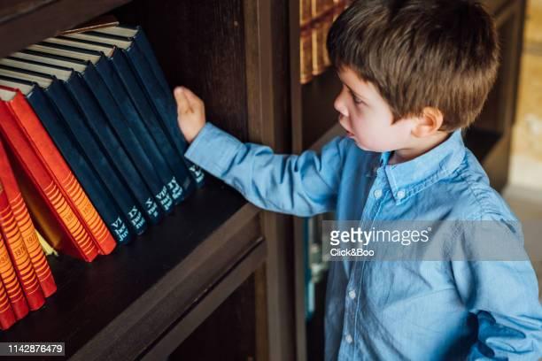 four years old kid looking for a book in a library (home interior) - click&boo fotografías e imágenes de stock