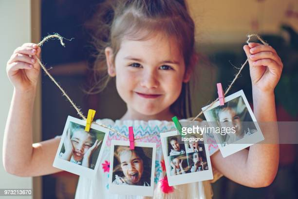 four years old little girl holding string of instant photos - 4 5 years stock pictures, royalty-free photos & images