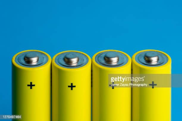 four yellow batteries on blue blackground - 電源 ストックフォトと画像