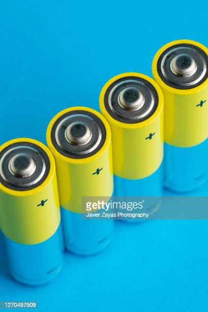 four yellow batteries on blue blackground - alkaline stock pictures, royalty-free photos & images