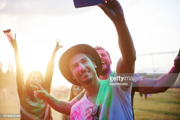 four young adult friends covered in coloured chalk powder taking selfie at holi festival - multi colored hat stock pictures, royalty-free photos & images