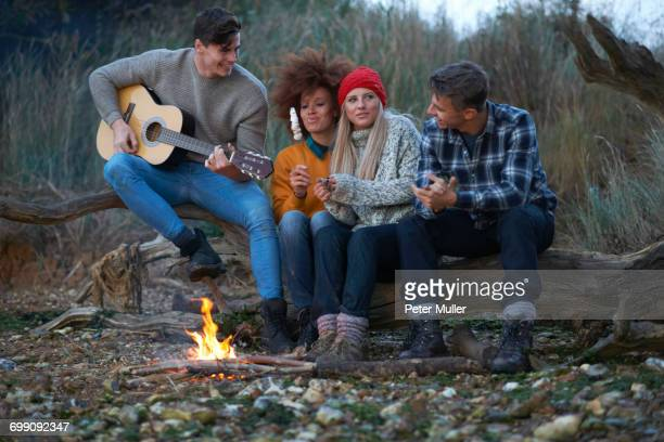 Four young adult friends playing guitar by campfire on beach at dusk