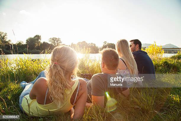 four young adult friends reclining on riverbank - waterkant stockfoto's en -beelden