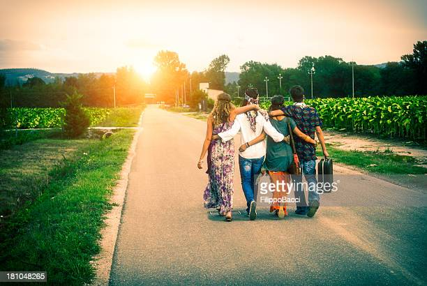 Four young adult hippie friends walking on countryside against sunset