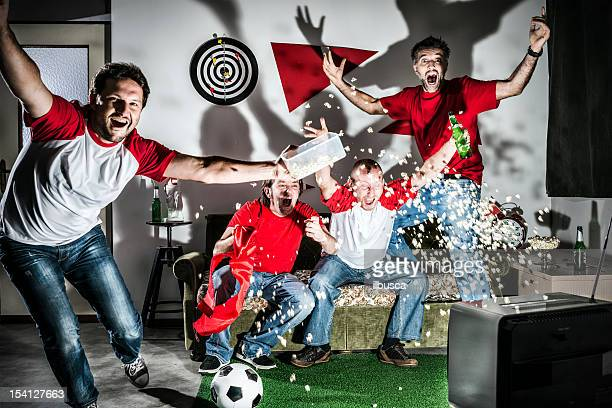 four young adult men friends watching football on television: goal! - match sport stock pictures, royalty-free photos & images