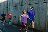 Four young adult runners running along city sidewalk