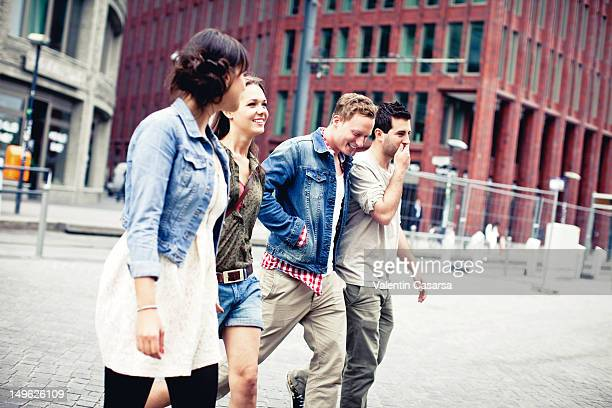 Four young adults crossing city street
