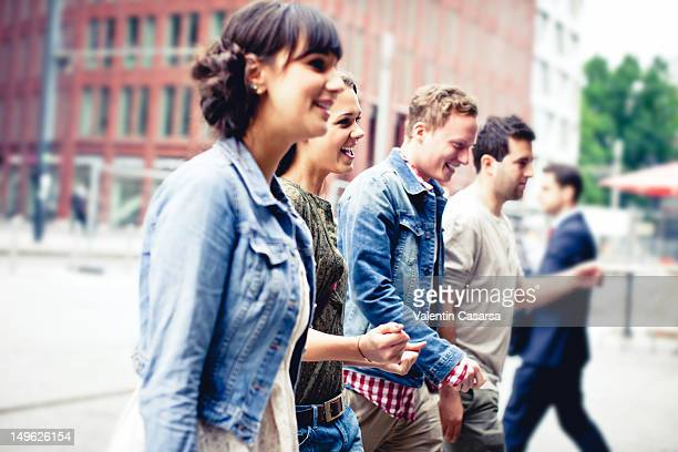 four young adults crossing city street - cadrage à la taille photos et images de collection