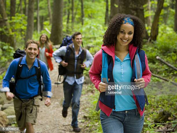 four young adults hiking in the forest - freundschaft stock pictures, royalty-free photos & images