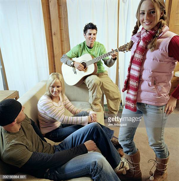 Four young adults indoors, man playing guitar, portrait of woman