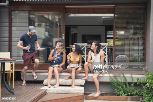 four young adults sitting on patio steps and young man with plate of food - patio doors stock pictures, royalty-free photos & images