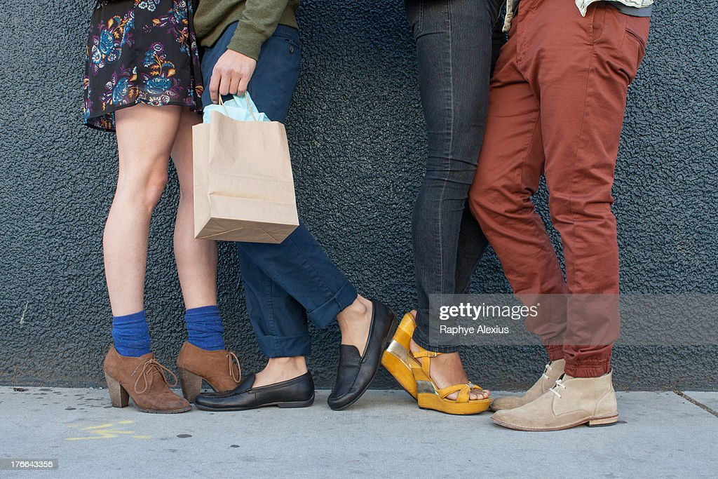 Four young adults standing by wall, low section : Stock Photo