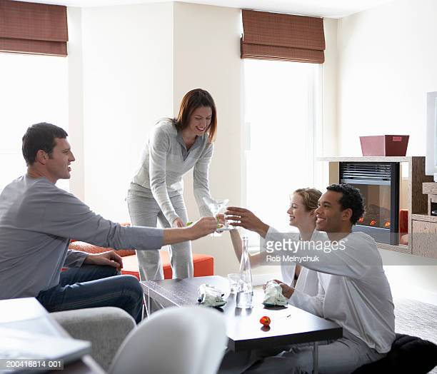 Four young adults toasting with cocktails in living room, smiling