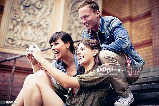 Four young adults using smart phone