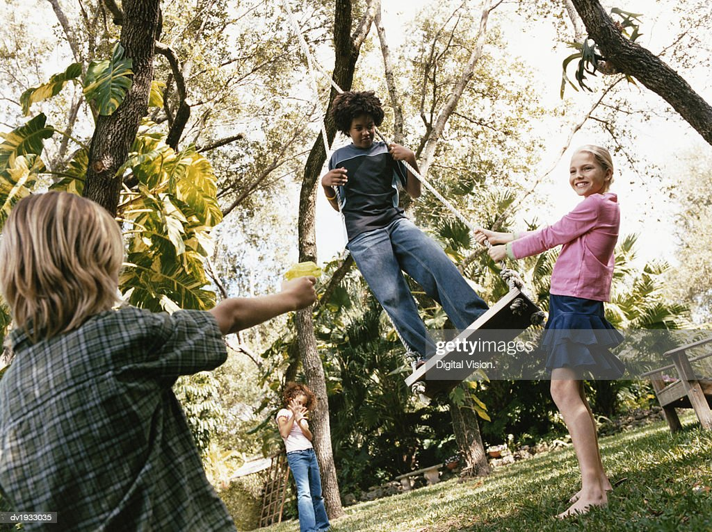Four Young Boys and Girls in a Garden, One of the Boys Standing on a Swing and Being Aimed at by a Boy With a Water Pistol : Stock Photo