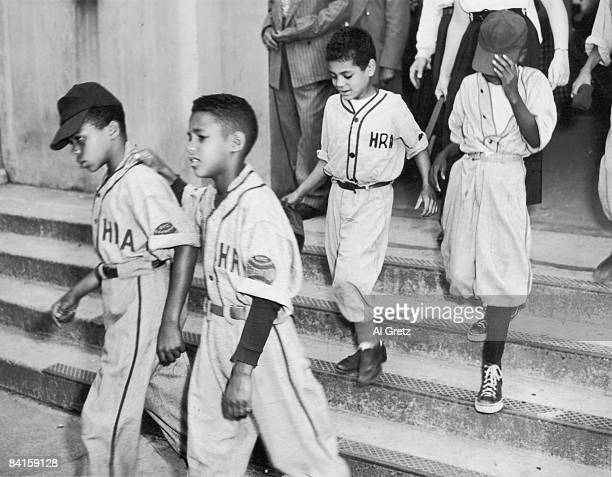Four young boys in baseball uniforms walk down the steps as leave Yankee Stadium after viewing the body of American baseball player Babe Ruth which...