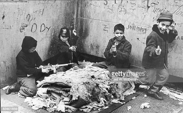 Four young boys three with toy guns and one with what appears to be a stapler play in a graffiti decorated corner outside the Aguilar Branch of the...