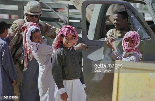 Four young boys, wearing thobes, with three in keffiyehs, beside a military truck with two soldiers in military fatigues in the Saudi–Iraqi neutral...