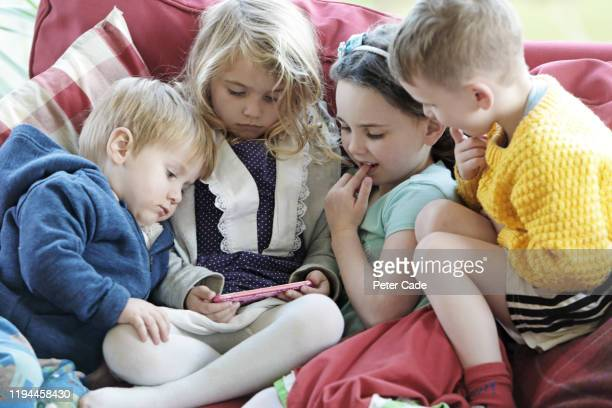 four young children on sofa looking at phone - bright stock pictures, royalty-free photos & images