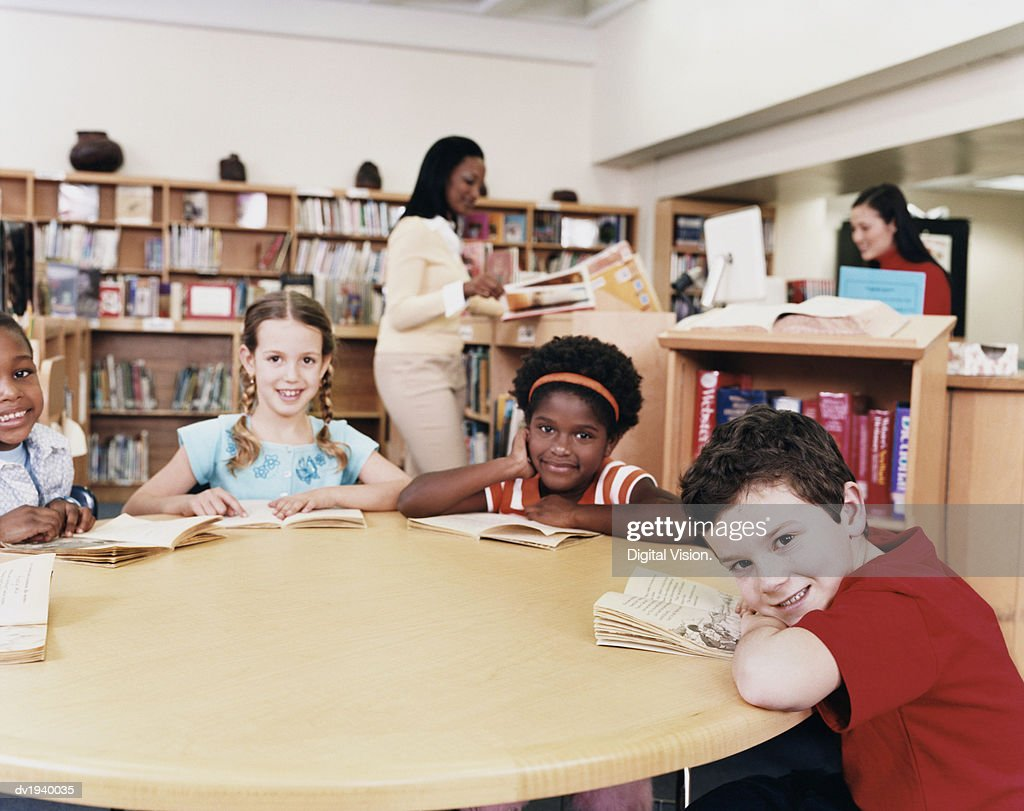 Four Young Children Sitting Around a Table in a Library : Stock Photo