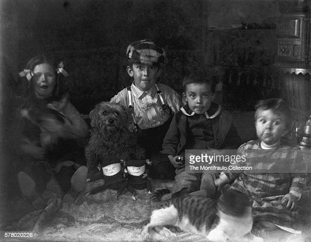 Four young children sitting with dog and cat in roomBeside them are two unusual looking homemade dolls Just above them is an ornamental stove Roton...
