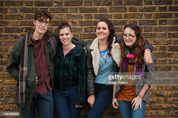 Four young friends against brick wall, smiling
